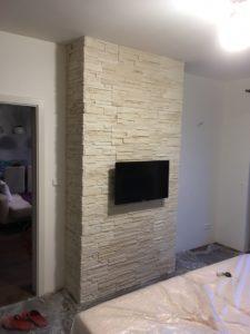 Obklad stěny v ložnici umělým kamenem. Usazení televize a zásuvek.